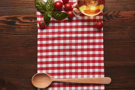 Photo for Top view of checkered tablecloth, wooden spoon and fresh basil with tomatoes and oil on wooden surface - Royalty Free Image