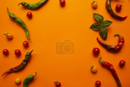 top view of fresh ripe tomatoes and chili peppers on orange background