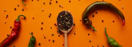 top view of fresh chili peppers and peppercorns in wooden spoon on orange
