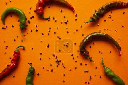top view of chili peppers and peppercorns on orange background