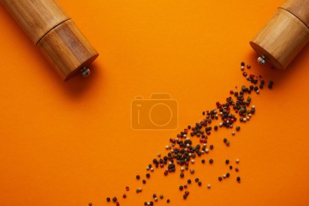 top view of spice containers and peppercorns on orange background