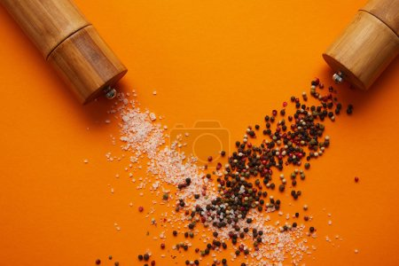 top view of spice containers and salt with peppercorns on orange