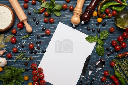 fresh raw vegetables, spices, blank card and rolling pin on wooden surface