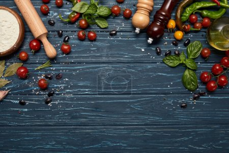 top view of fresh raw vegetables, spices and rolling pin on wooden background