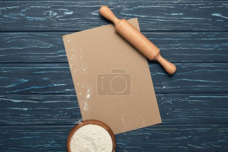 top view of blank card, rolling pin and bowl with flour on wooden surface
