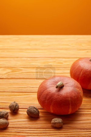 close-up view of ripe orange pumpkins and walnuts on wooden surface