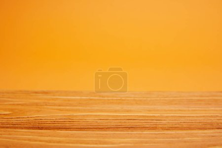 empty wooden surface and bright orange background