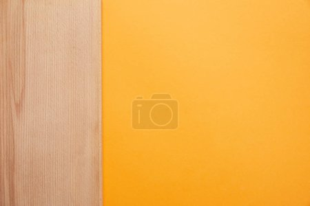 Photo for Top view of bright orange background and wooden surface - Royalty Free Image