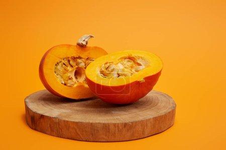 Photo pour Vue rapprochée de citrouille tranchée mûre sur une planche ronde en bois sur fond orange - image libre de droit