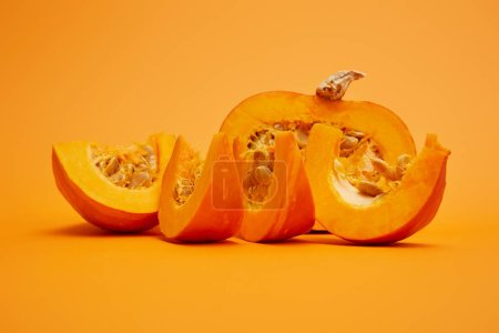 raw ripe sliced pumpkin with seeds on orange background