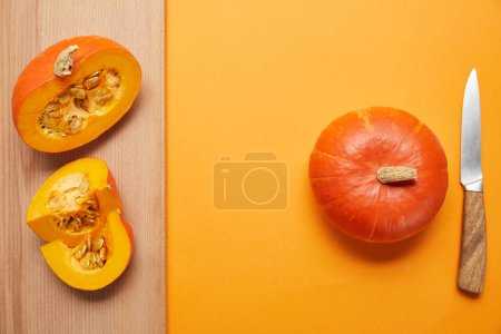 top view of whole and sliced pumpkins and knife on orange and wooden surface