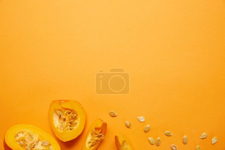 top view of raw ripe sliced pumpkin with seeds on orange background
