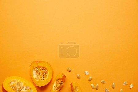 Photo pour Vue de dessus de crus mûr citrouille en tranches avec des graines sur fond orange - image libre de droit