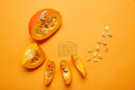 Photo pour Vue de dessus de citrouille tranchée mûre avec des graines sur fond orange - image libre de droit