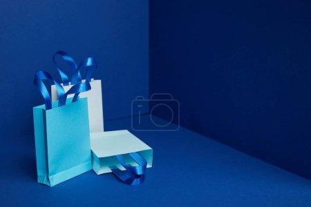 Photo pour Vue rapprochée des sacs à provisions en papier disposés sur fond bleu - image libre de droit