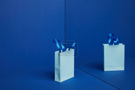close up view of paper shopping bag with mirror reflection on blue backdrop