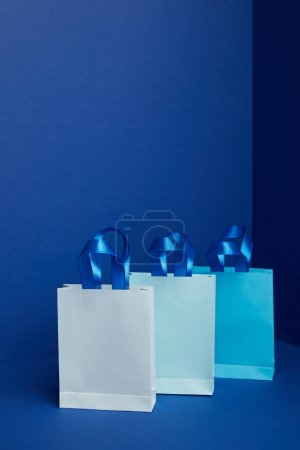 Photo for Close up view of paper shopping bags arranged on blue backdrop - Royalty Free Image