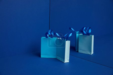 close up view of arranged paper shopping bags with mirror reflection on blue background