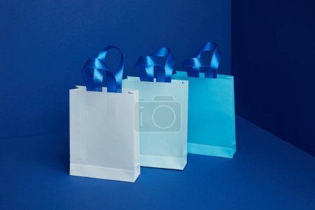 close up view of paper shopping bags arranged on blue backdrop