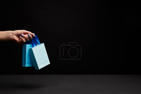 partial view of woman holding blue paper shopping bags on black background