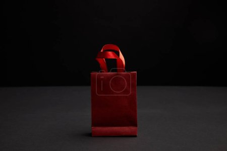 close up view of red paper shopping bag on black backdrop