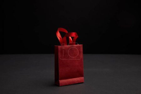 Photo for Close up view of red paper shopping bag on black backdrop - Royalty Free Image