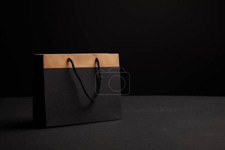 close up view of paper shopping bag on black backdrop