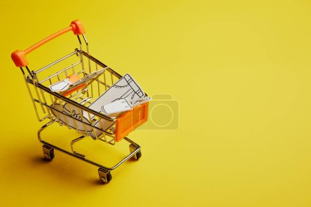 close up view of little shopping cart with clothes made of paper on yellow background