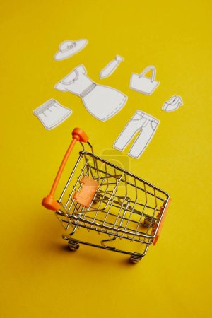 close up view of little shopping cart and clothes made of paper on yellow background