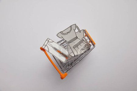 top view of shopping cart with little clothes made of paper on grey background