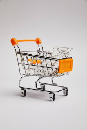 close up view of shopping cart with little clothes made of paper on grey background