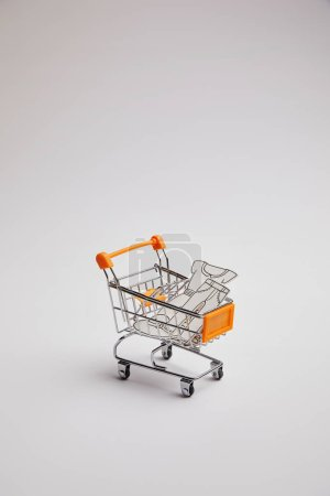close up view of shopping cart with little goods made of paper on grey background