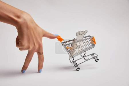 cropped shot of female hand and little shopping cart with paper clothes on grey background