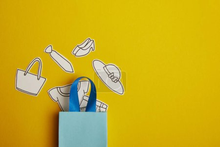 top view of blue shopping bag with paper clothes on yellow background