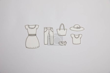 top view of arranged paper clothes isolated on grey, shopping concept
