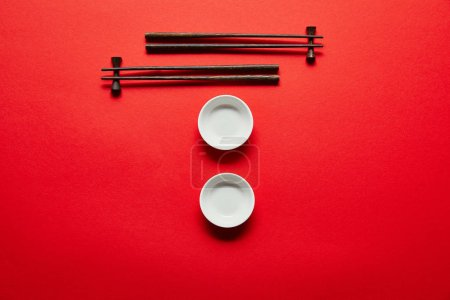 flat lay with arranged empty bowls and chopsticks on red background