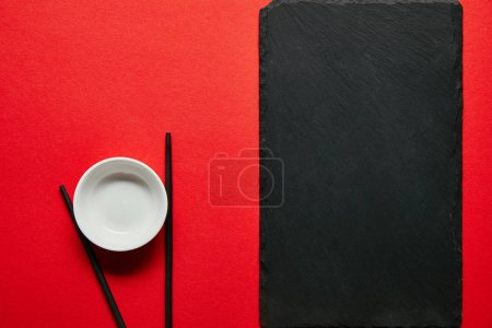 top view of arranged empty bowl, chopsticks and slate plate on red background