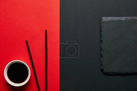 top view of soya sauce in bowl, chopsticks and slate plate on red and black background