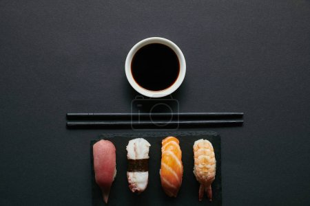 top view of assorted nigiri sushi set, chopsticks and soya sauce on black slate plate on dark tabletop