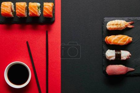 Photo pour Lay plat avec sauce de soja dans le bol, des baguettes et des sushis définit sur plaques ardoises noires sur fond rouge et noir - image libre de droit