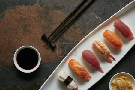 top view of assorted nigiri sushi set, chopsticks and soya sauce on white plate on dark surface