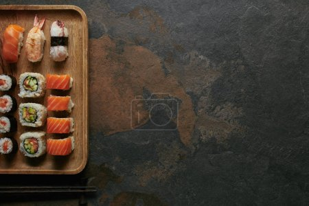 top view of arranged sushi set on wooden plate and chopsticks on dark surface