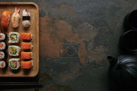 Photo for Flat lay with sushi set on wooden plate, black teapot and cups on dark tabletop - Royalty Free Image