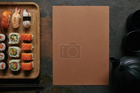 flat lay with sushi set on wooden plate, black teapot and cups on dark tabletop