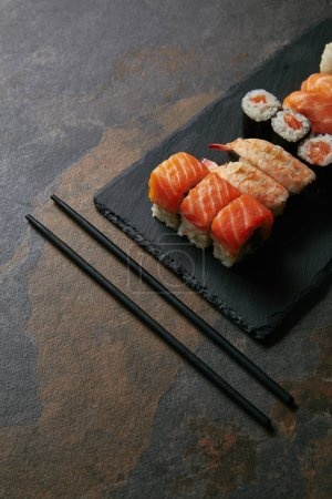 close up view of arranged sushi set on black slate plate and chopsticks on dark surface
