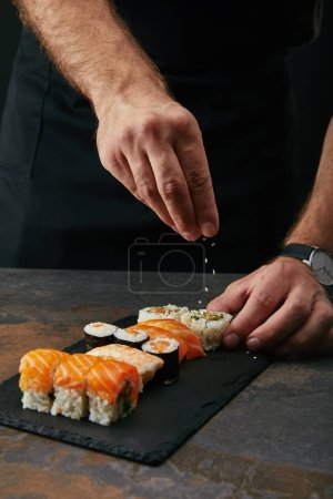 Photo for Partial view of chef pouring sesame seeds on arranged sushi set on slate plate on dark tabletop - Royalty Free Image