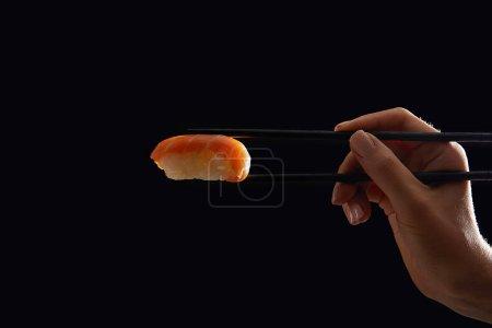 Photo pour Recadrée hot de femme tenant nigiri sushi au saumon isolé sur fond noir - image libre de droit