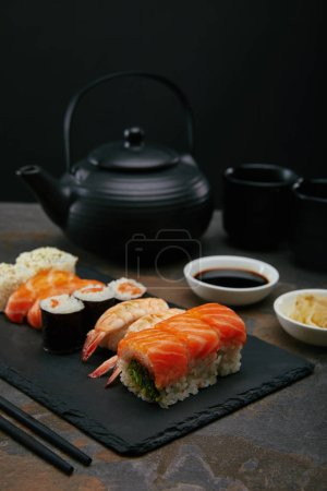 food composition with sushi set, ginger and soya sauce in bowls, teapot and cups with tea on dark surface