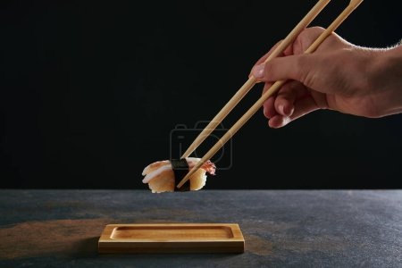 partial view of woman holding nigiri sushi with shrimp on black background