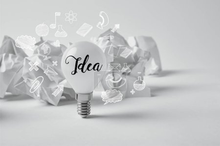 Photo for Light bulb with crumpled papers on white with idea sign and icons - Royalty Free Image